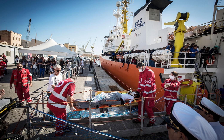 Menschen mit medizinischen Beschwerden, wie dieser Mann, der von Mitarbeitern des italienischen Rote Kreuzes in einer Trage getragen wird, waren die ersten, die die Aquarius in Palermo, Italien, verließen. 13. Oktober 2017