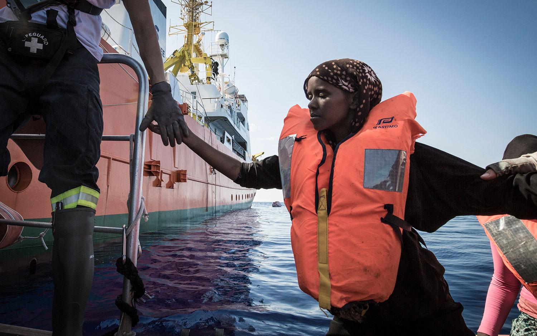Rettungskräfte der SOS MEDITERRANEE helfen einer Somalierin von dem Festrumpfschlauchboot (RHIB), damit sie an Bord der Aquarius gelangen kann. 11. Oktober 2017.