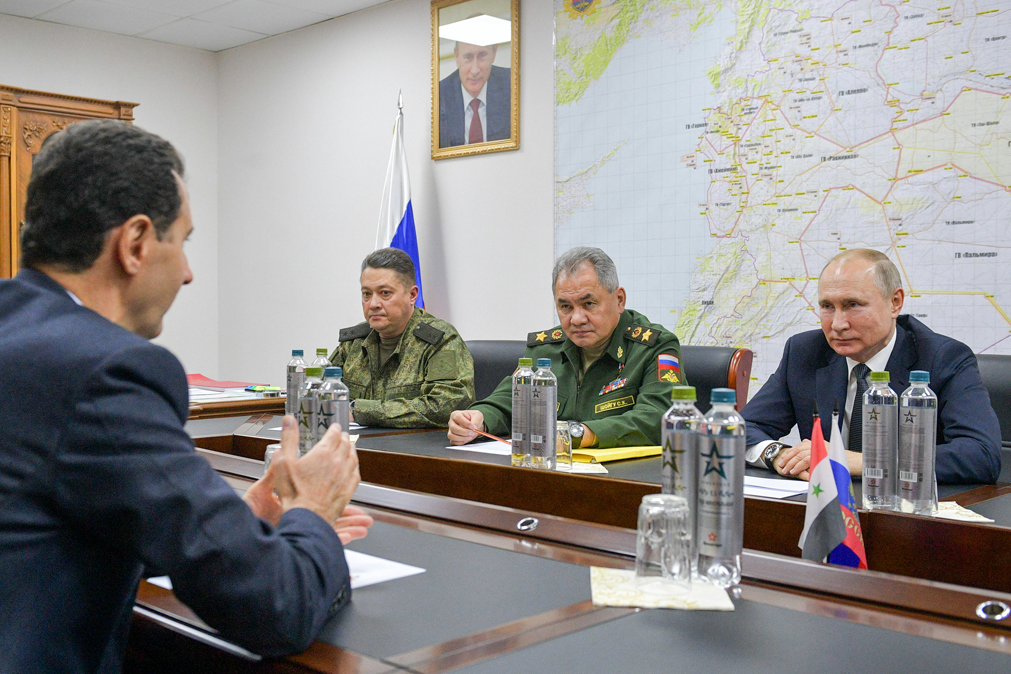 Syria's President Bashar al-Assad (left), Russia's President Vladimir Putin (right), Minister of Defense Sergei Shoigu (second right), and Lieutenant-General Alexander Yuryevich Chaiko (third right) during a meeting.